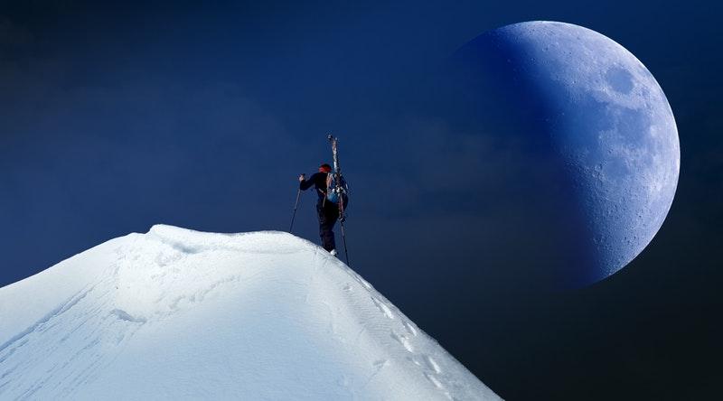 雪山の山頂を登る人