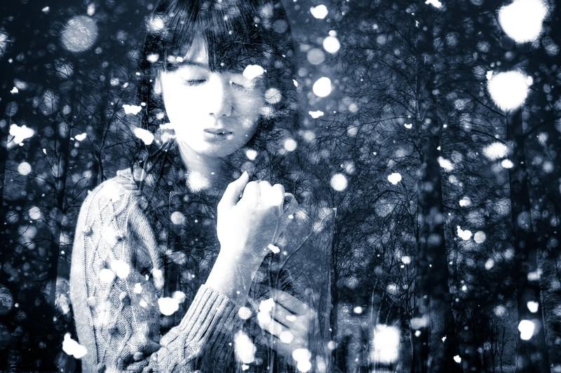 雪の中で目を閉じている少女