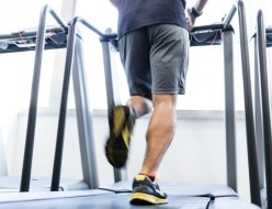 ランニングマシンでトレーニングしている男性