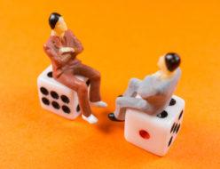 サイコロの上で対話している2人の男性のイメージ